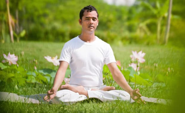 man meditating in field